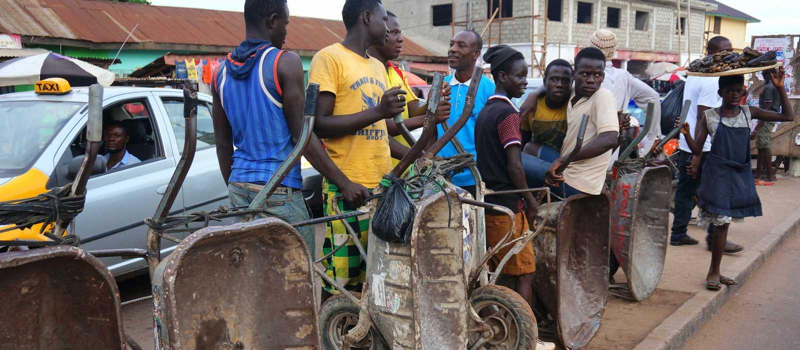 Jugendliche warten am Straßenrand mit Schubkarren