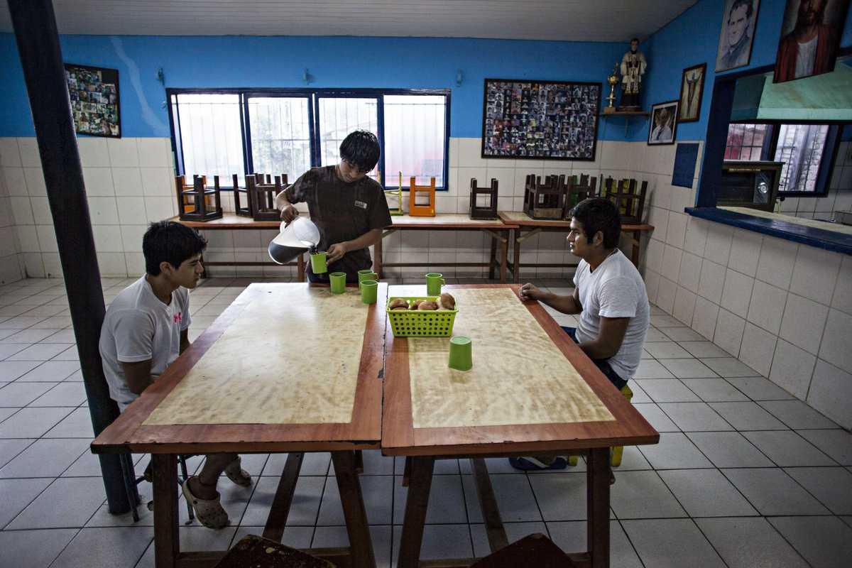 Armando mit zwei Jungen bei der Vorbereitung des Frühstück