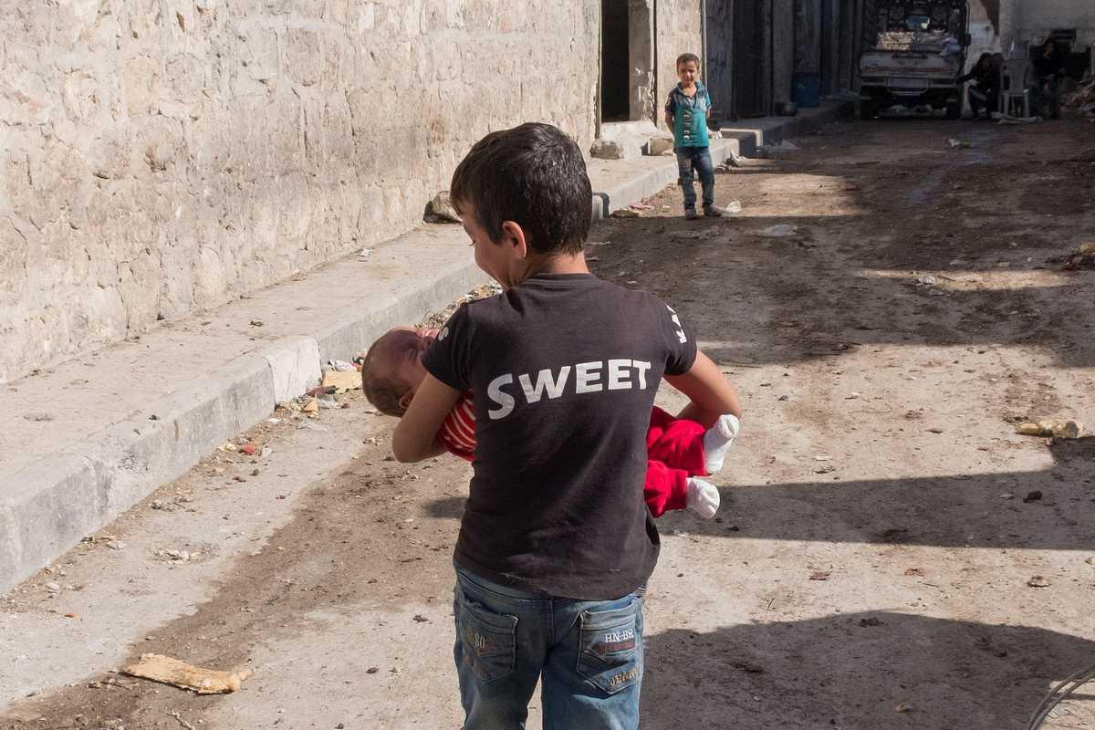 Ein kleiner Junge trägt ein Baby durch die zerstörte Stadt