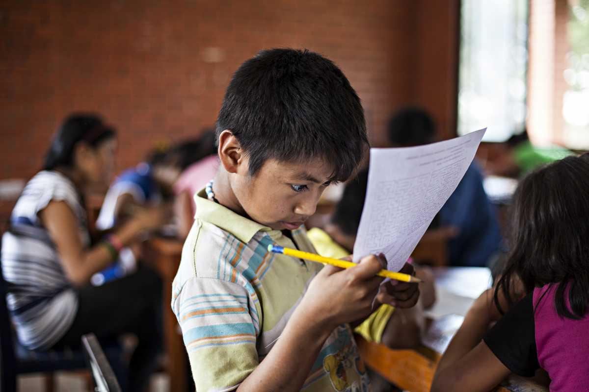 Álvaro schaut im Unterricht konzentriert auf ein Blatt Papier.