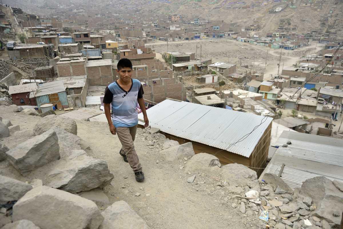 Ein Junge geht auf einem Berg hoch. Im Hintergrund sind Blechhütten des Slums zu sehen.