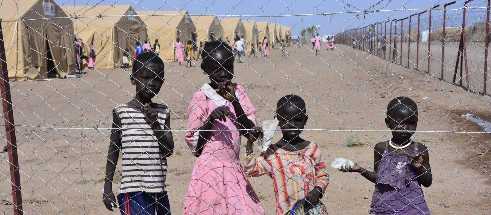 Kinder hinter einem Drahtzaun vor einem Flüchtlingslager