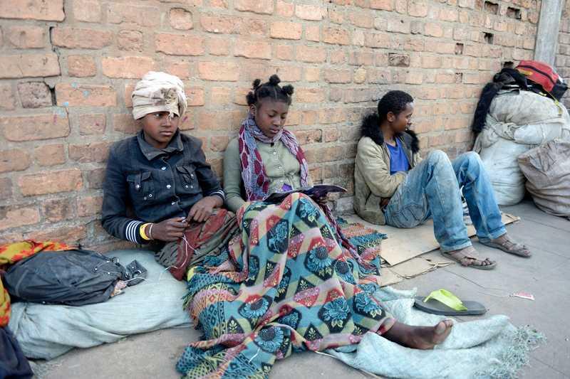 Jugendliche, die am Straßenrand sitzen und sich notdürftig mit Decken warm halten