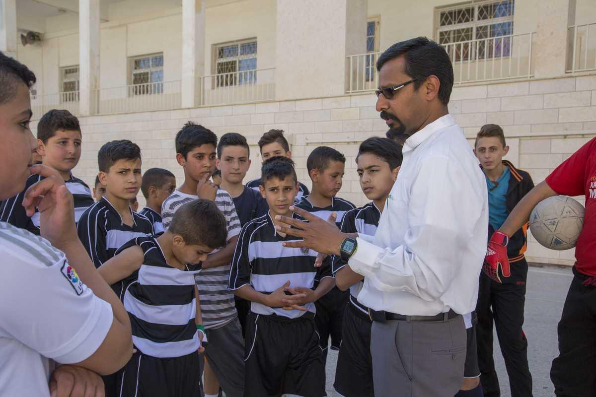 Pater Raj spricht mit einer Gruppe Jungen im Fußballtrikot