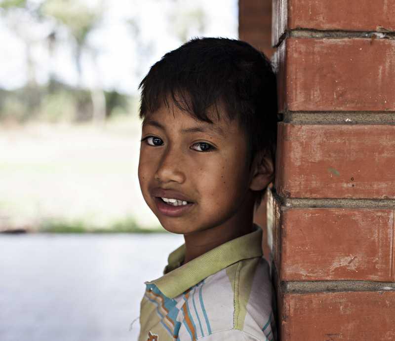 Álvaro, der mit dem Rücken an eine Backsteinwand lehnt.