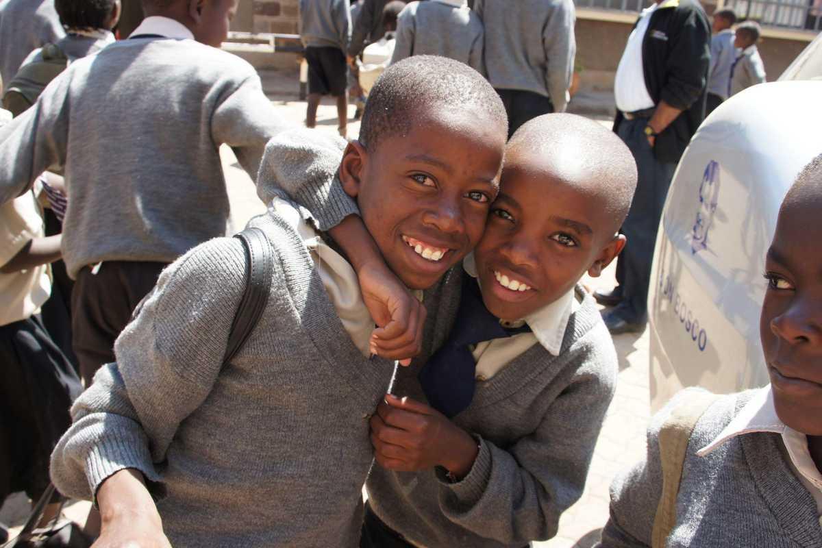Zwei Jungen in Schuluniform, die sich umarmen