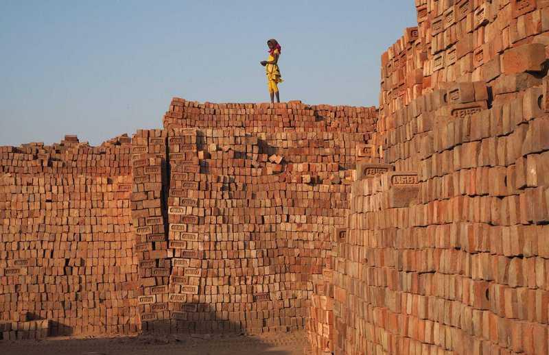 Kind steht auf einer Mauer aus Ziegeln in einer Ziegelfabrik