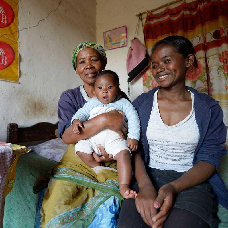 Elisa sitzt gemeinsam mit ihrer Mutter und ihrem Sohn auf einer Bettkante
