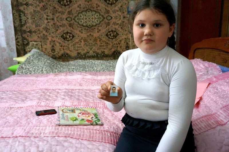 Ana sitzt auf ihrem Bett und hält ein Bild ihrer Mutter in der Hand