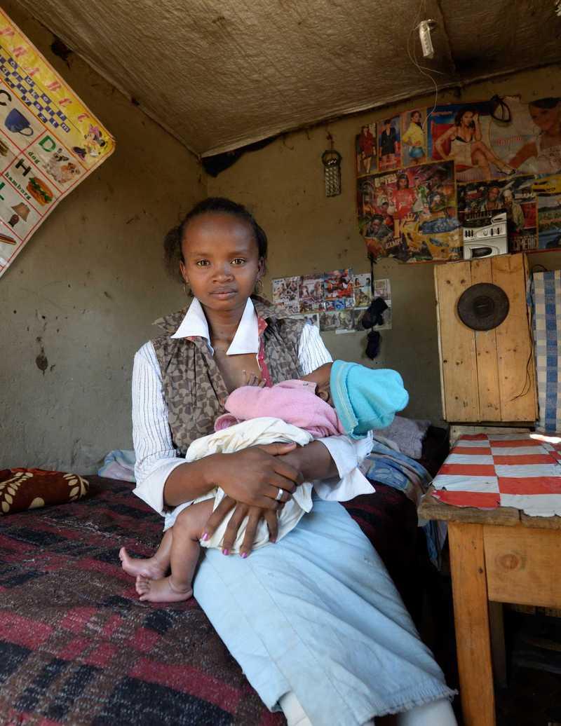 Martine sitzt mit ihrer Tochter in ihrem kleinen Zimmer.