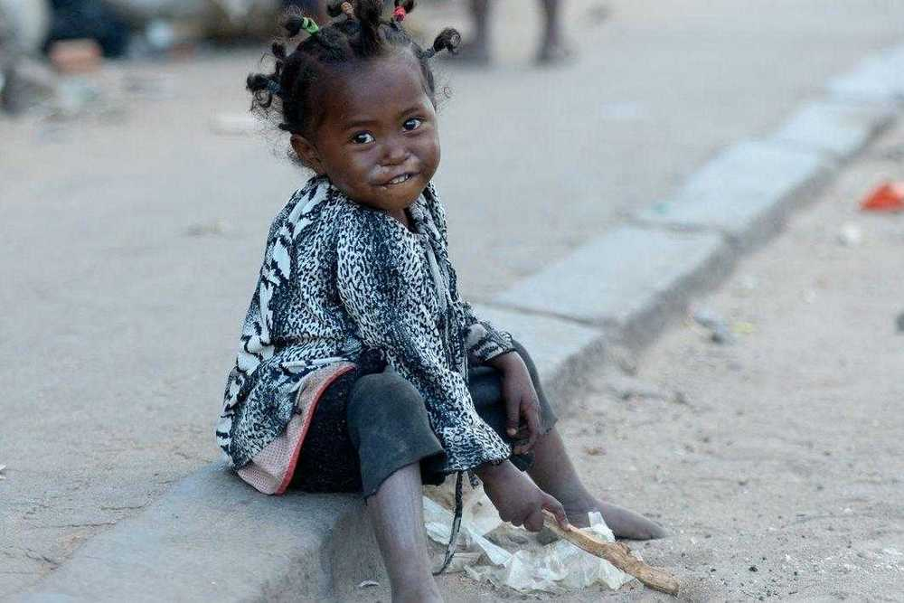 Ein kleines Mädchen, das am Straßenrand im Staub spielt