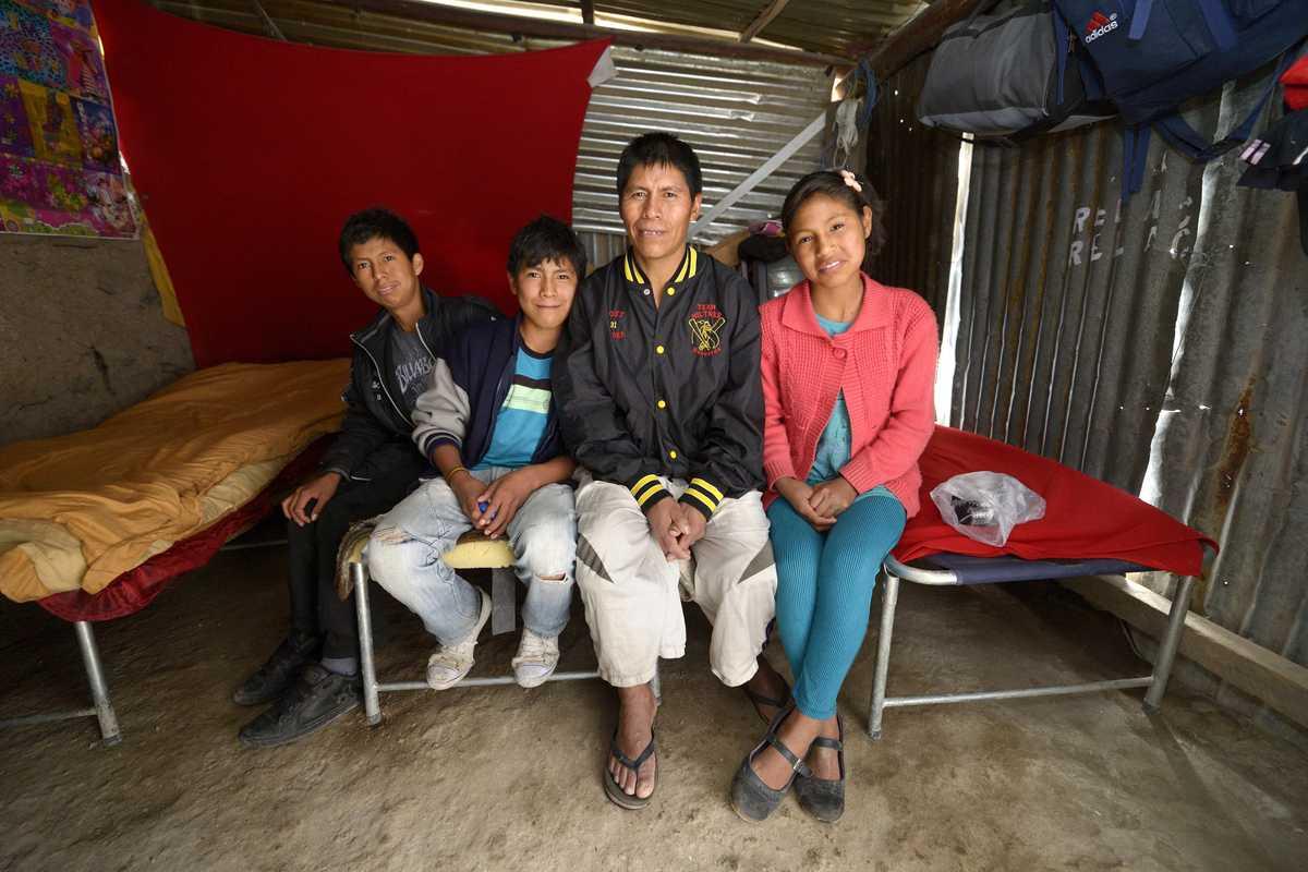 Vater mit Tochter und zwei Söhnen sitzen auf einer Bettkante in einer Blechhütte