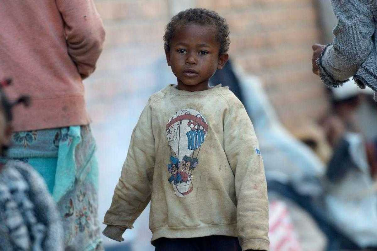 Ein kleiner Junge in verschlissener Kleidung auf der Straße