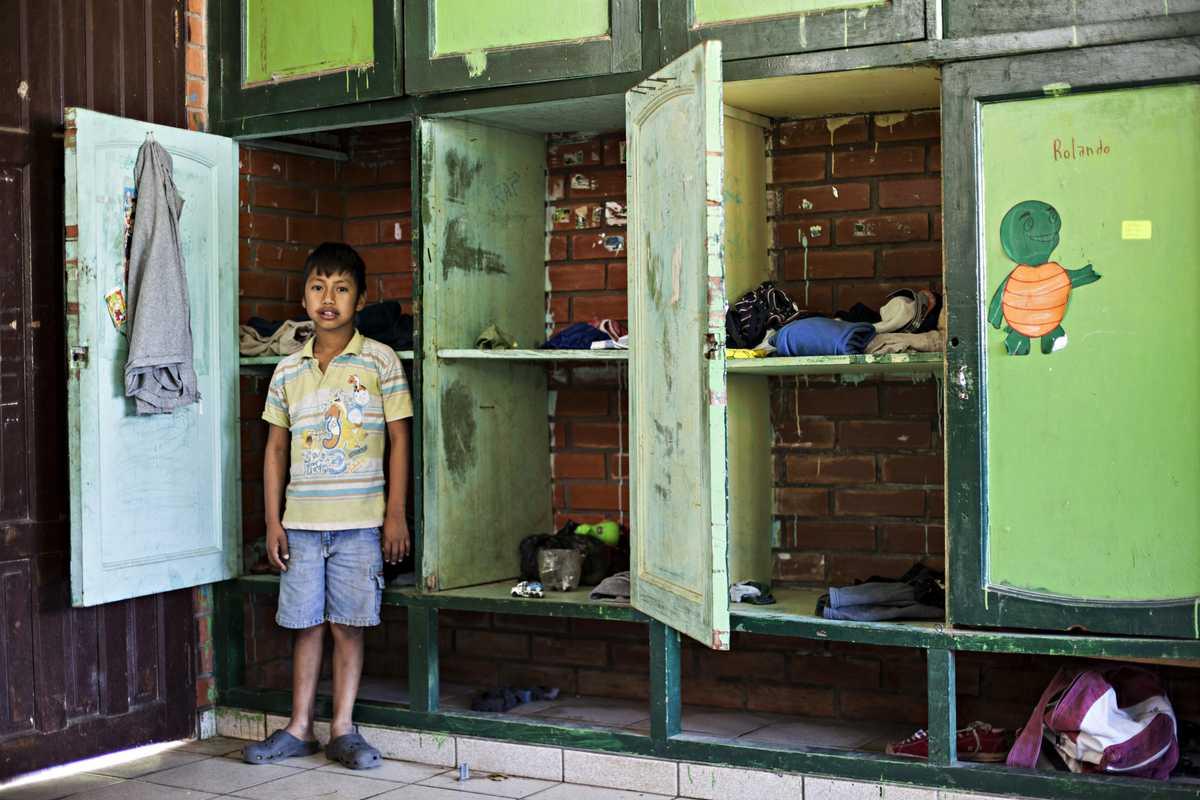 Álvaro steht vor grünen Kleiderspinden im Schlafsaal