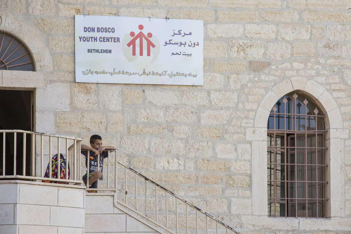 Kleiner Junge sitzt auf den Treppen des Eingangs vom Don Bosco Zentrum