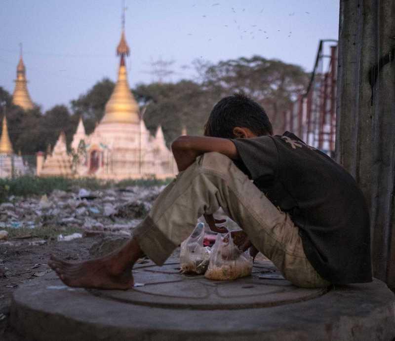Ein Junge kauert auf dem Boden vor einer goldenen Pagode