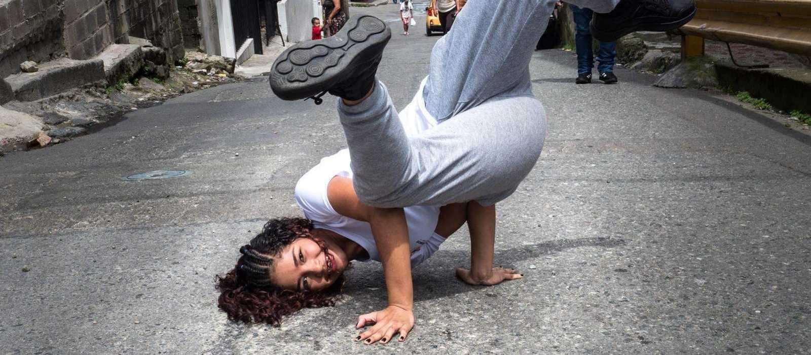 Mädchen macht Kopfstand auf einer Straße in Medellín