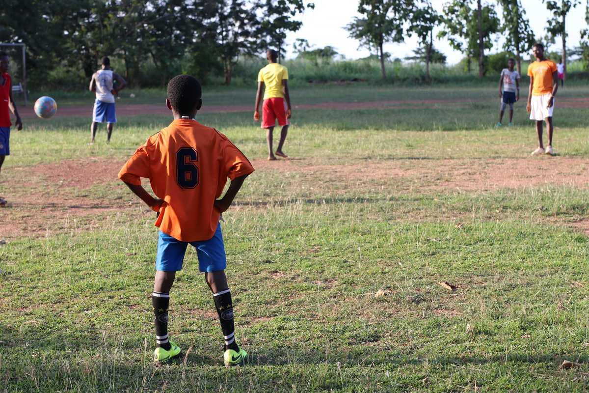 Kind in Trikot steht am Rande eines Fußballfelds