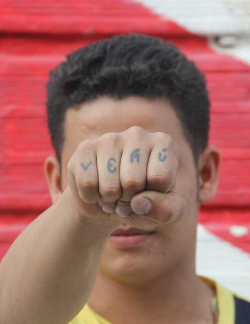 Junge verdeckt Gesicht mit Faust, deren Finger tätowiert sind