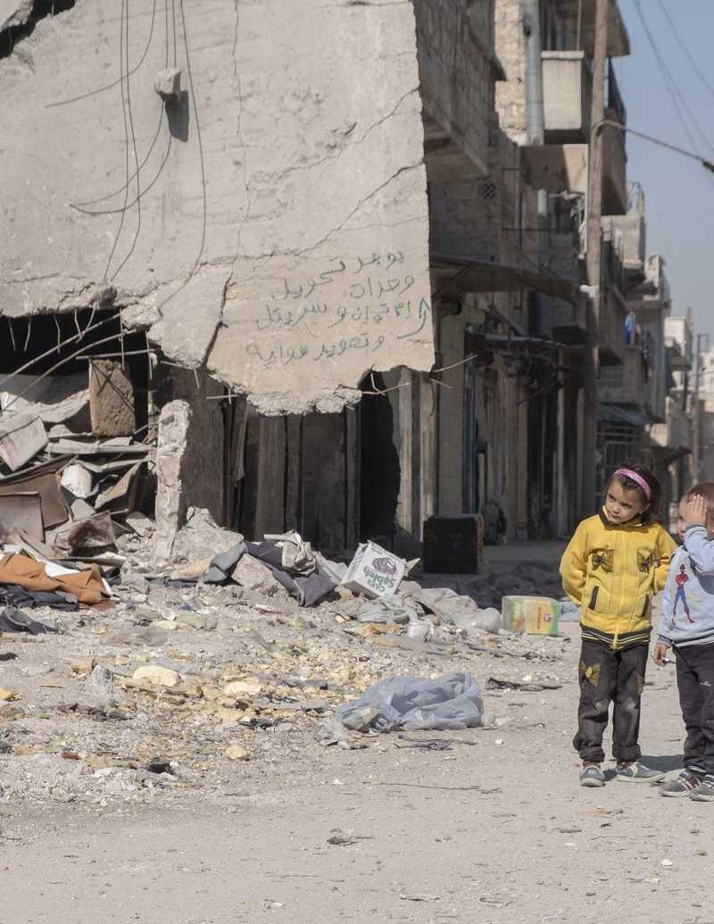 Ein kleiner Junge und ein Mädchen stehen vor den Trümmern von Aleppo