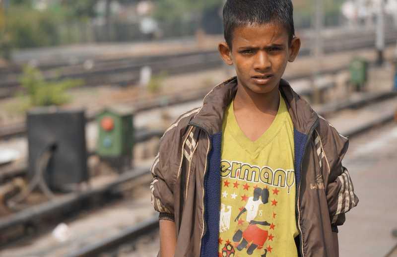 Junge steht an einem verlassenen Bahnsteig