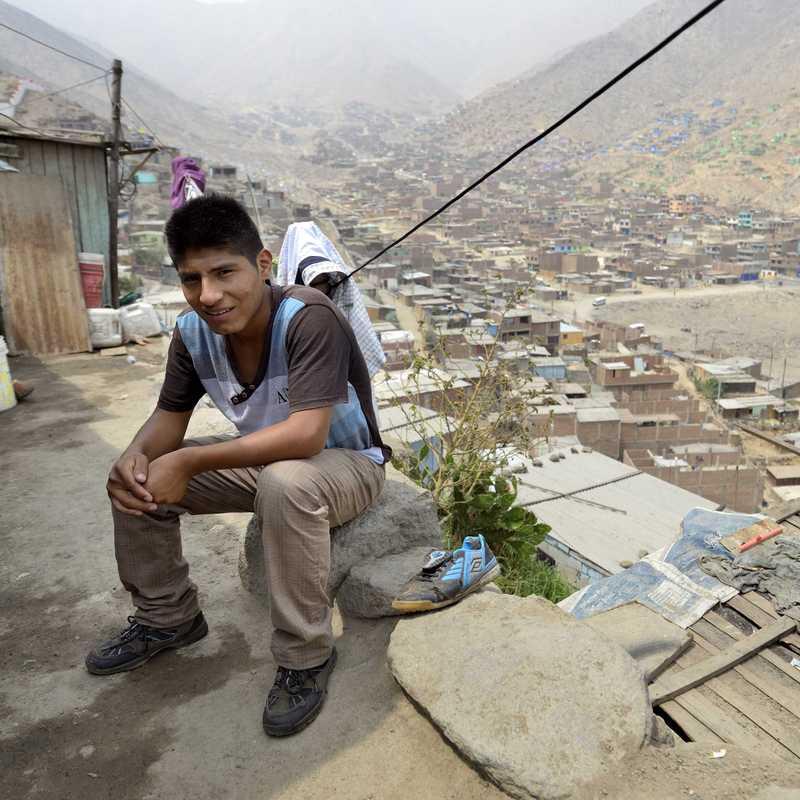 Ein Junge sitzt an einem steinernen Wegrand. Hinter ihm die Dächer der Blechhütten.