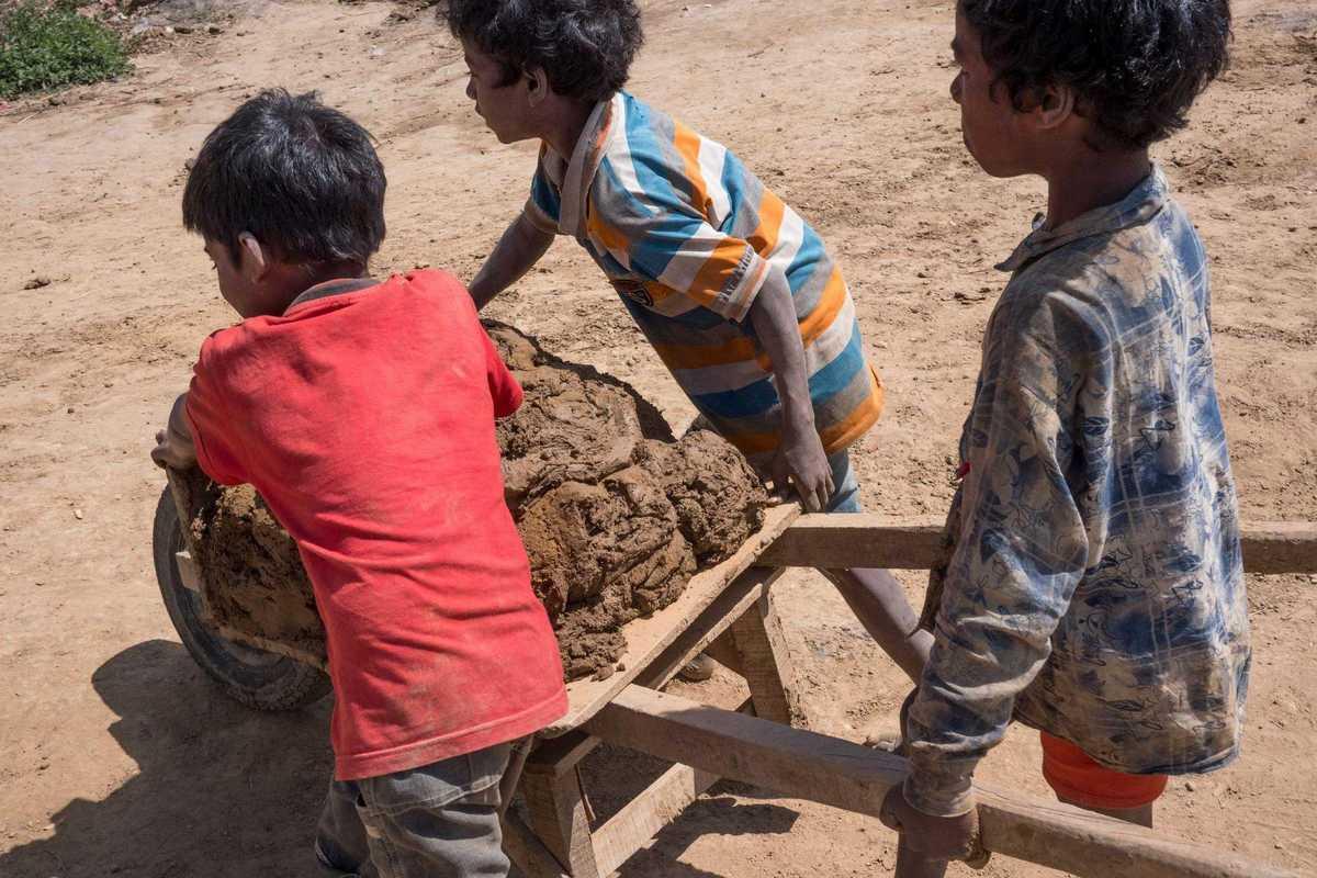 Drei Jungen schieben eine Schubkarre mit Lehm