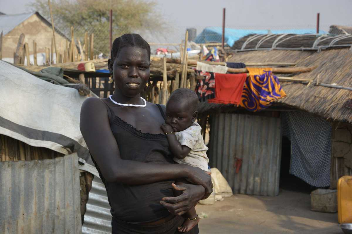 Frau mit Kind auf dem Arm steht zwischen Zelten