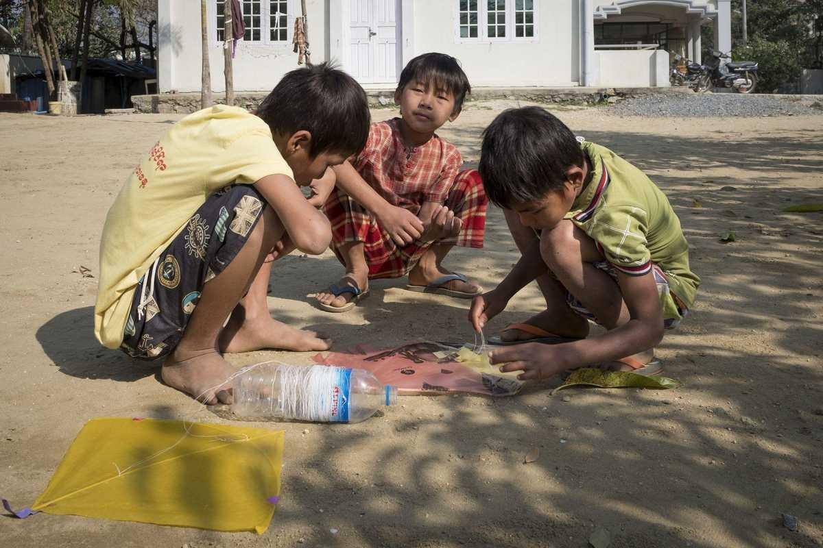 Drei kleine Jungen basteln einen Papierdrachen
