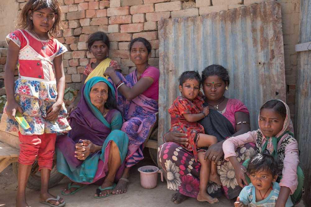 Eine Gruppe Frauen und Mädchen vor Ziegelhütten