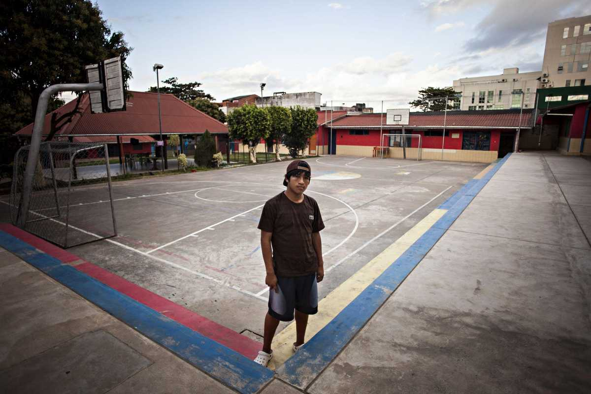 Armando steht auf einem asphaltierten Fußballfeld