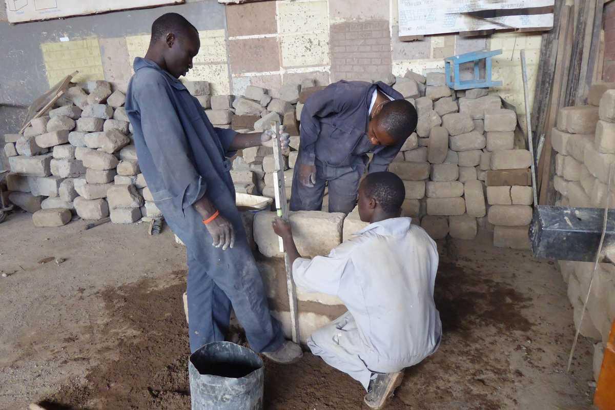 Drei Jugendliche bauen eine Mauer aus Steinen