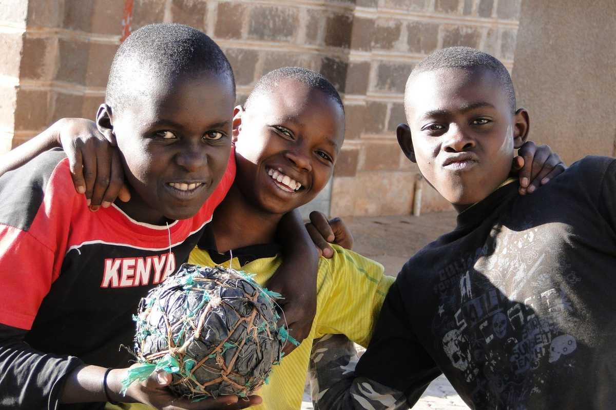 Drei Jungen mit einem zerfledderten Fußball