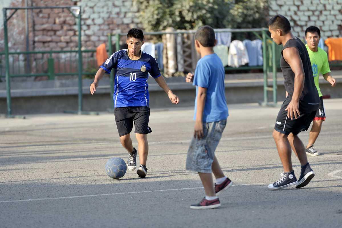 Drei Jungen spielen Fußball auf Asphalt