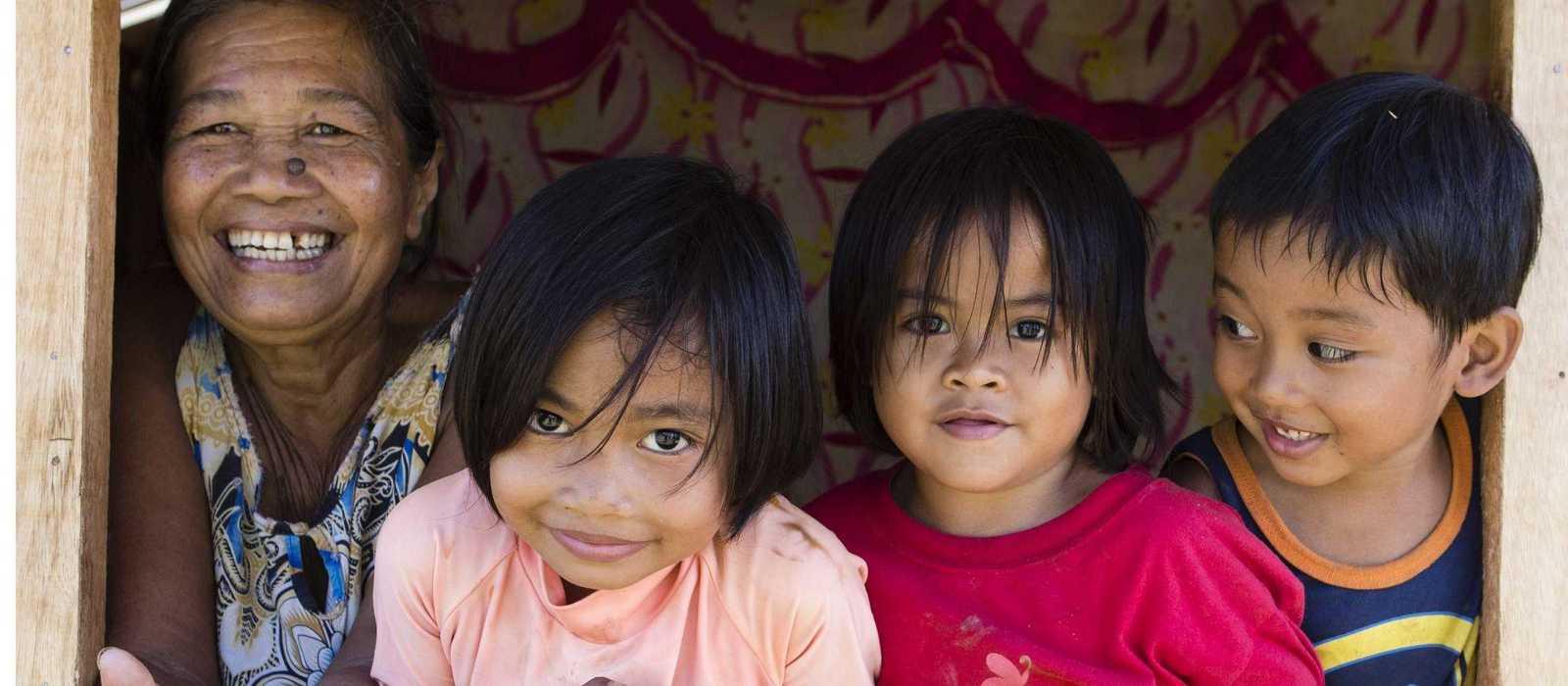 Drei Kinder schauen mit Großmutter aus einem Holzhaus