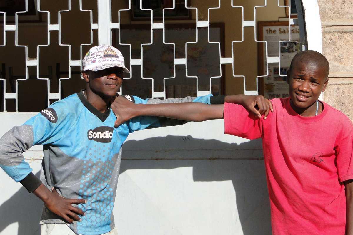 Zwei Jugendliche posieren vor einer Mauer