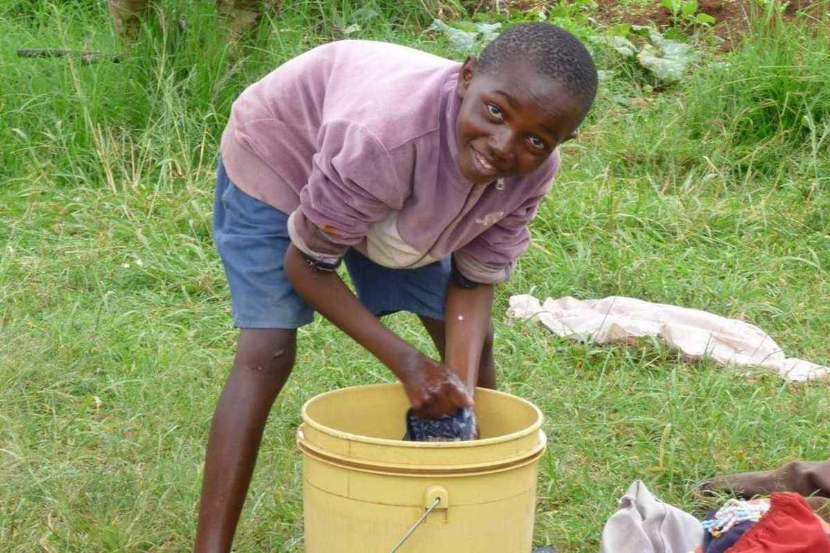 Ein Junge wäscht Kleidung in einem Eimer