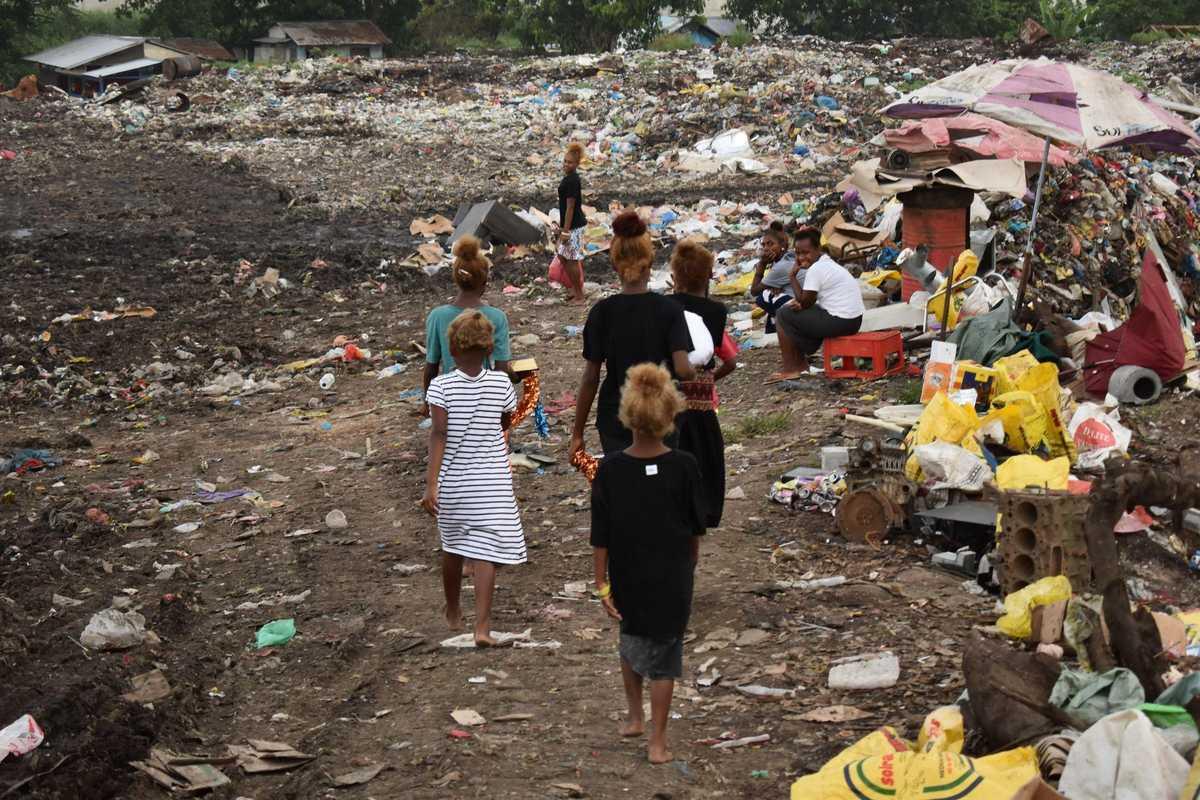 Frauen und Kinder laufen über die Müllberge