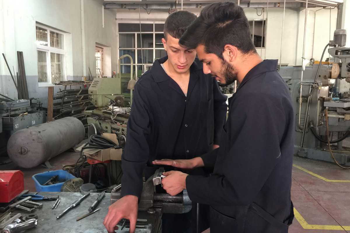 Zwei Jugendliche in Blaumann an einer Werkbank