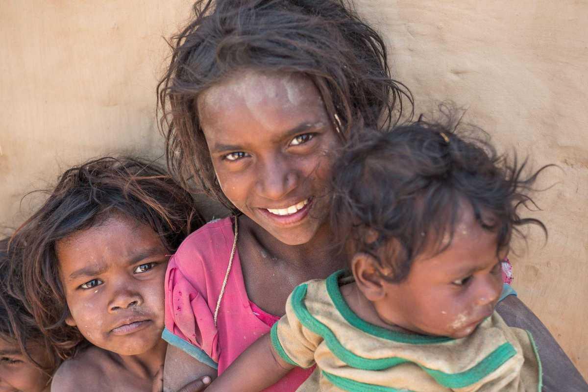 Ein Mädchen mit zwei kleinen Kindern vor einer Ziegelwand