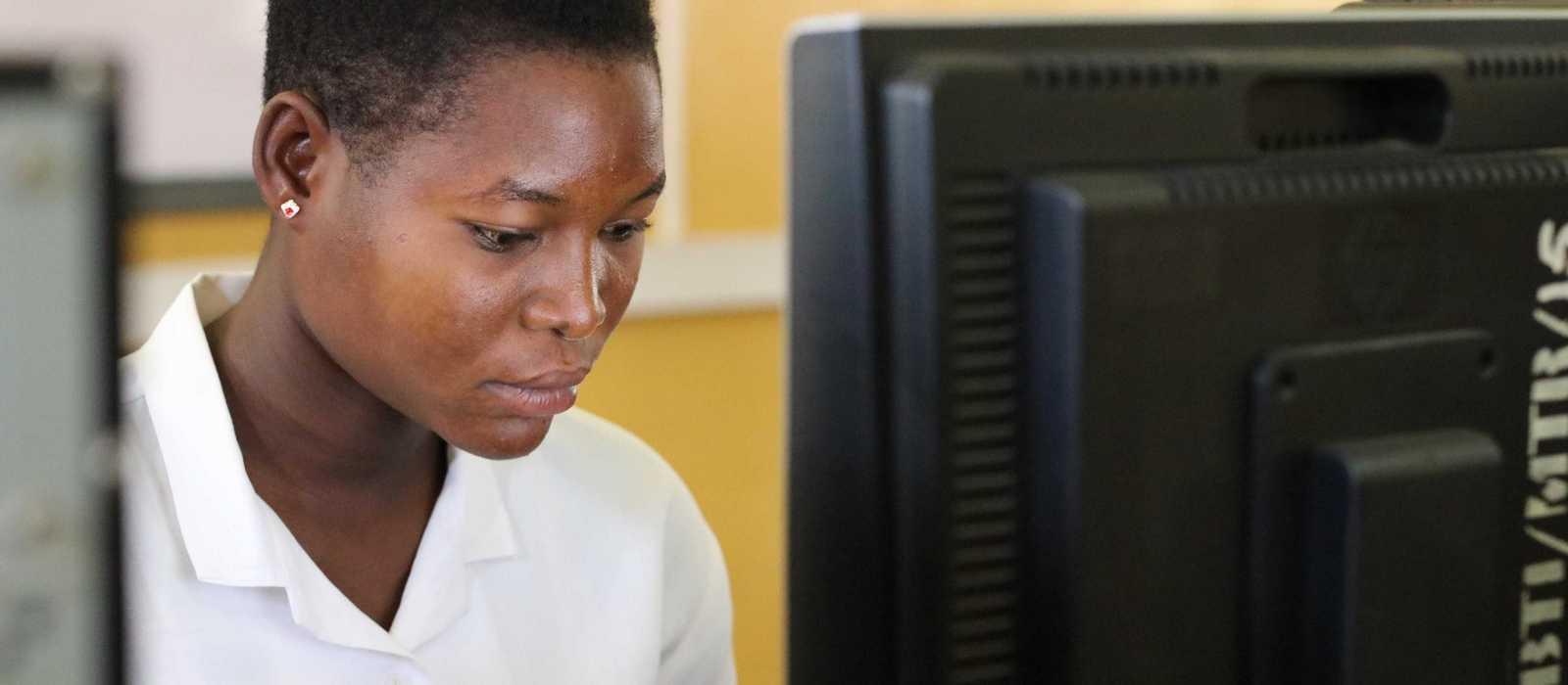 Mädchen sitzt hinter einem Computer-Bildschirm