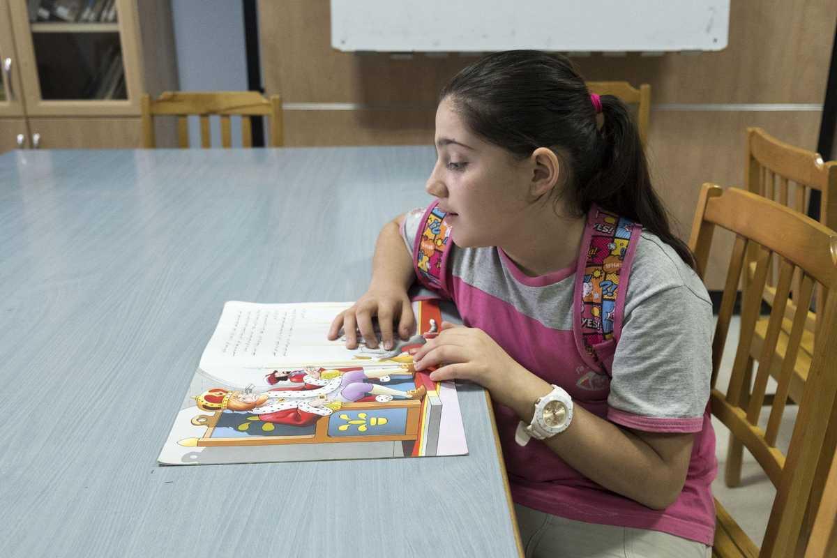 Ein junges Mädchen sitzt an einem Tisch und liest