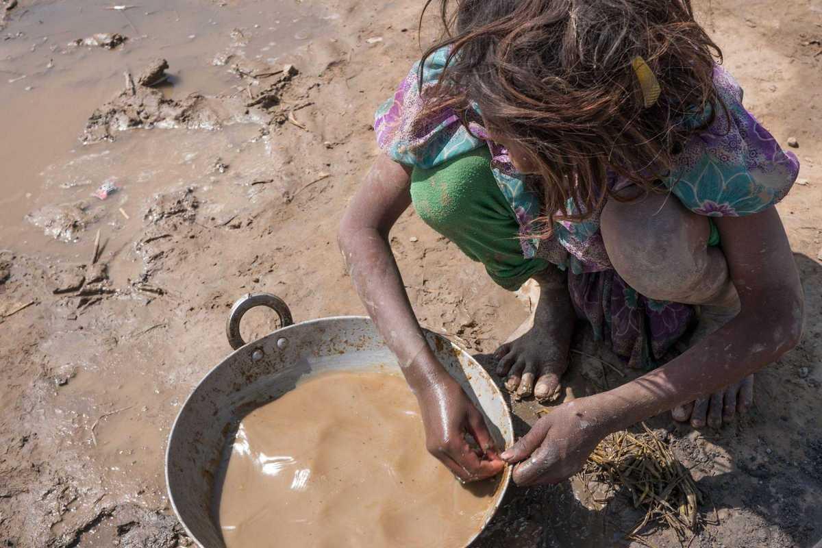 Mädchen hockt vor einem Eimer mit Wasser und Lehm