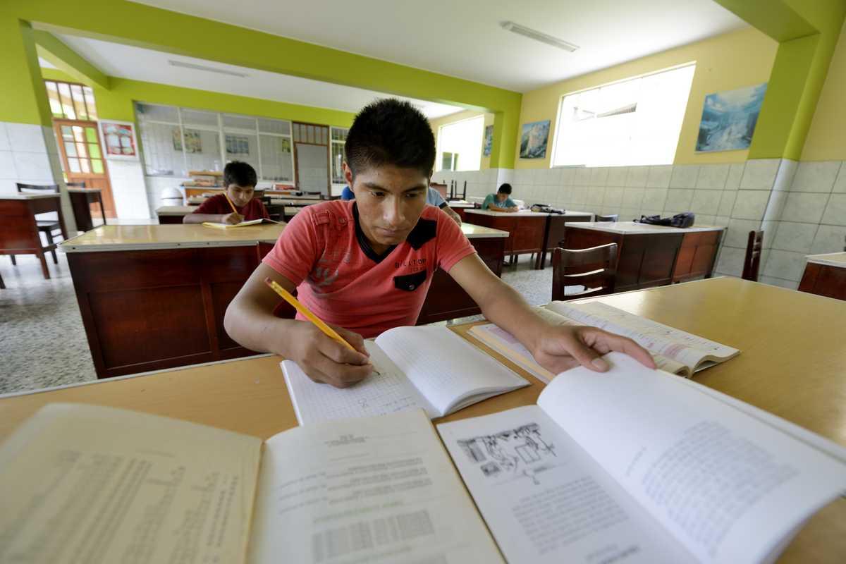 Ein Junge am Schreibtisch, vor ihm seine Unterrichtsmaterialien ausgebreitet.