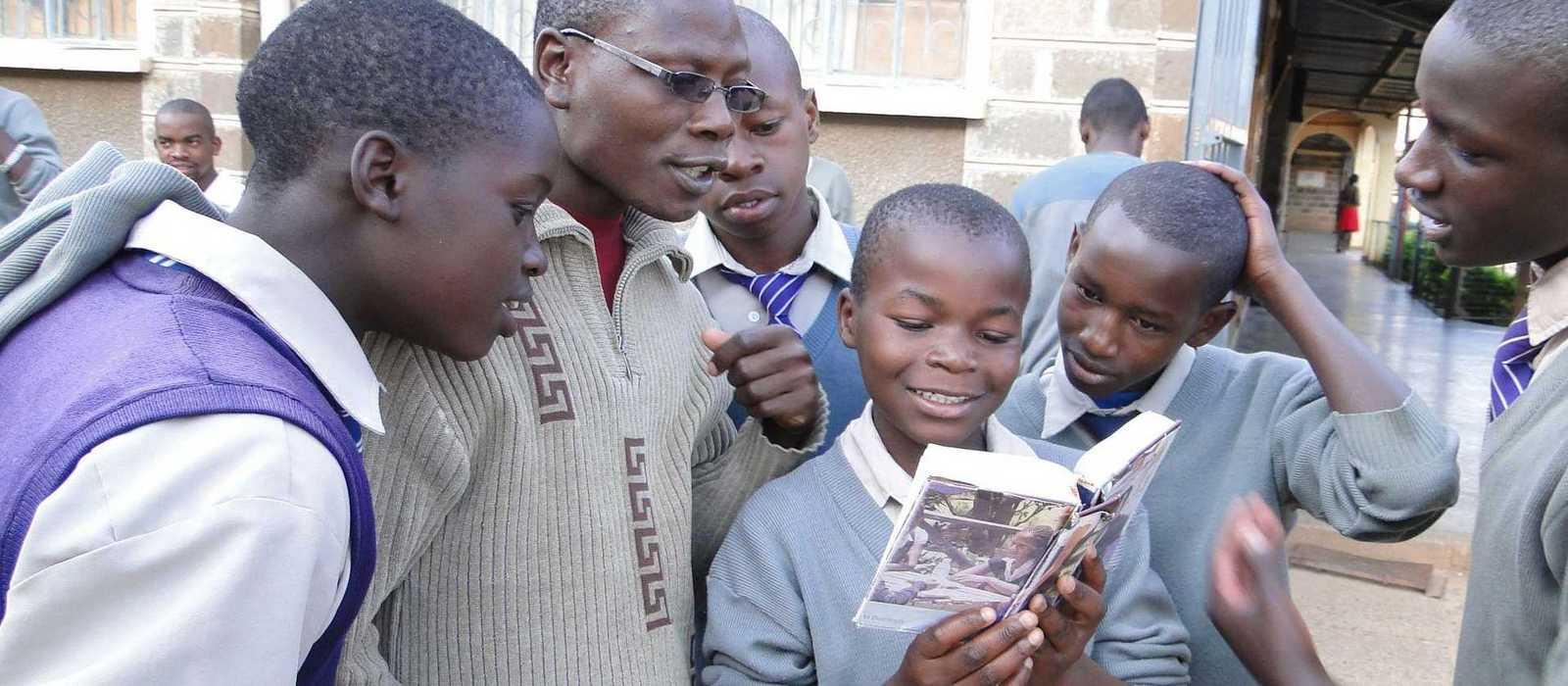 Eine Junge liest in einem Buch, andere stehen neugierig drumherum