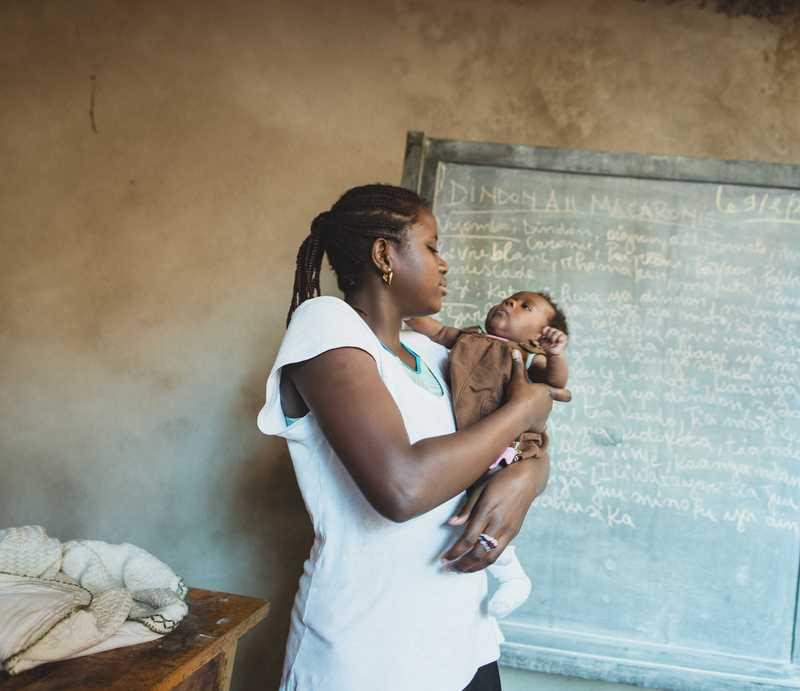 Gentille mit ihrem Baby vor einer alten Schultafel