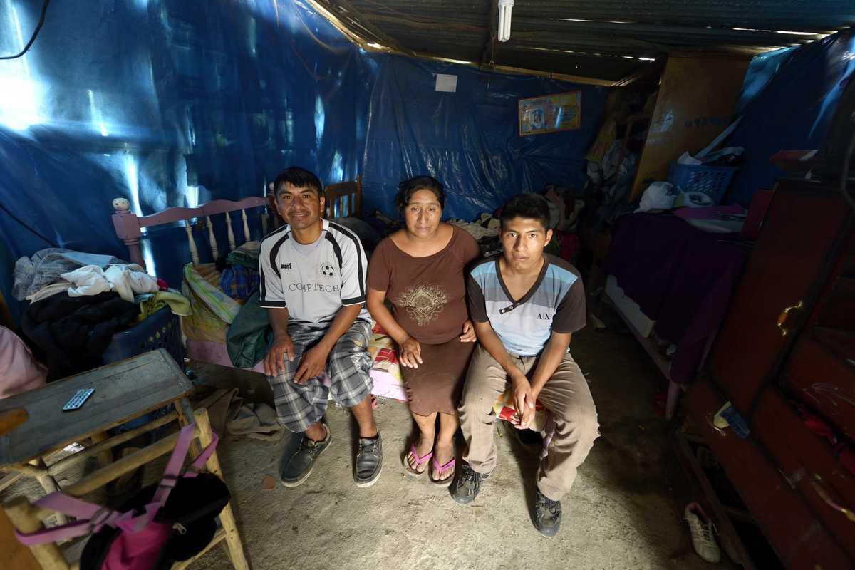 Ein Mann, eine Frau und ein Junge sitzen auf einer Liege im Innern einer Blechhütte.