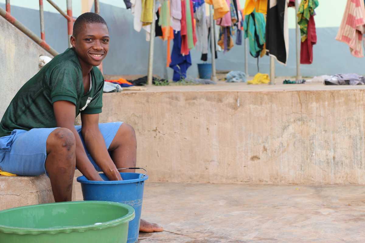 Jugendlicher wäscht Wäsche in einem Eimer