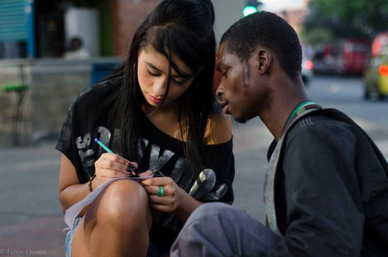 Mädchen hockt auf der Straße und schreibt einem Jungen etwas ins Schulheft