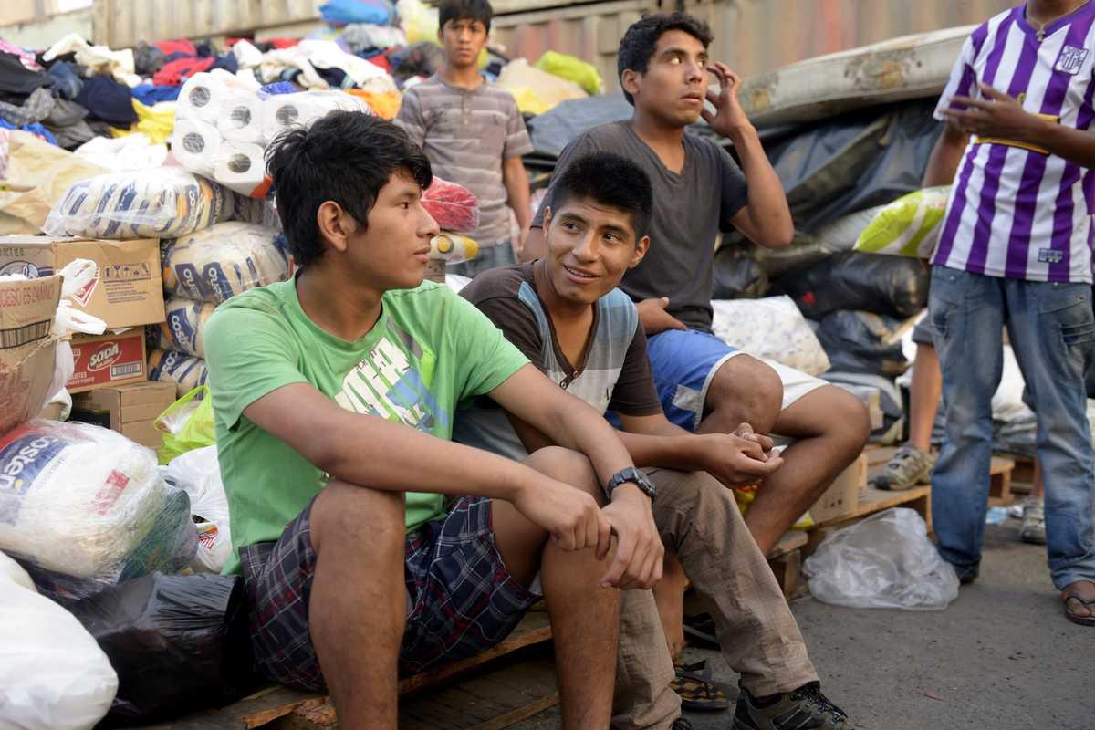 Drei Jungen, die vor einem Berg Sachspenden sitzen.